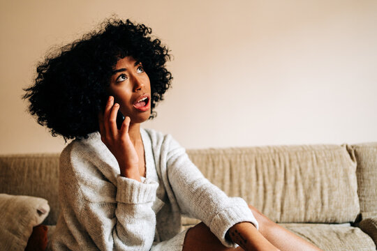 Funny black woman speaking on smartphone at home