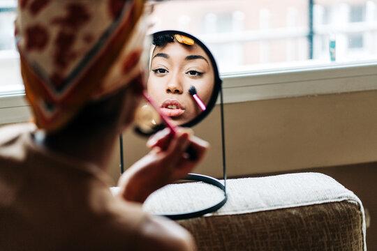 Black woman doing makeup at home
