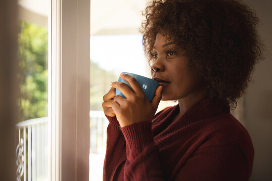 Thoughtful african american woman standing at sunny window drinking coffee and smiling