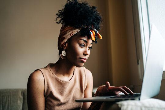 Black female freelancer working on laptop at home