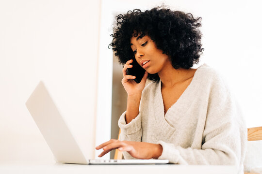 Black woman talking on smartphone and working on laptop at home