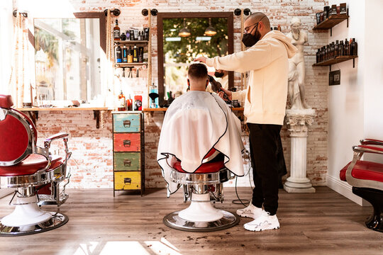 Stylish barber cutting hair of unrecognizable client in salon