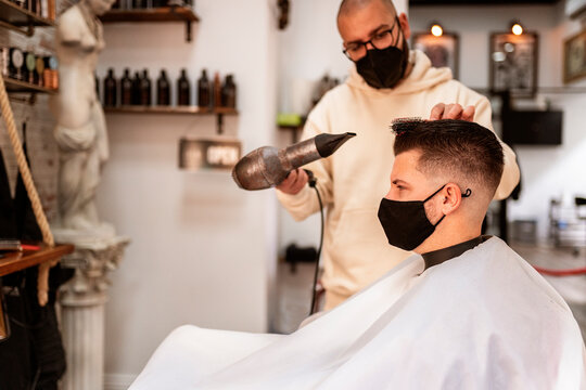 Barber with client using hair dryer in salon