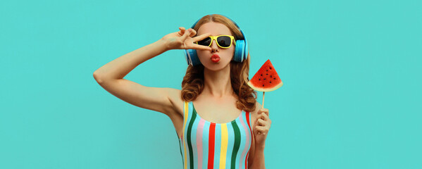 Summer colorful portrait of stylish young woman in headphones listening to music with juicy lollipop or ice cream shaped slice of watermelon, model blowing her lips posing on blue background