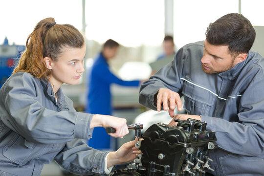 woman and man mechanic checking an engine