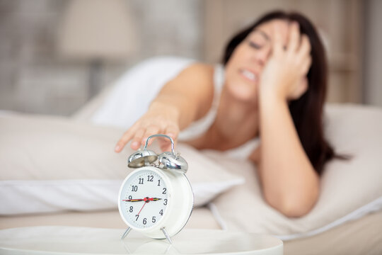 young sleepy woman turning alarm clock off