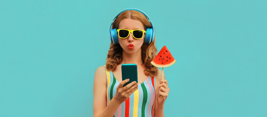 Fototapeta Summer colorful portrait of stylish young woman in headphones listening to music on smartphone with juicy lollipop or ice cream shaped slice of watermelon on blue background obraz