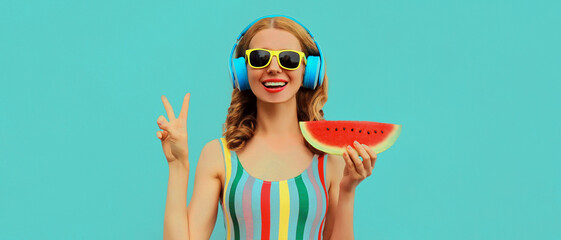 Fototapeta Summer colorful portrait of cheerful happy smiling young woman model posing in headphones listening to music with juicy slice of watermelon on a blue background obraz