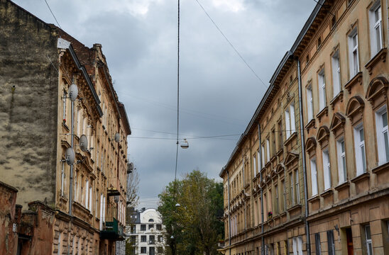 Streetscape street of historic Lviv city during day with yellow old vintage buildings in local residential neighborhood alley in old town