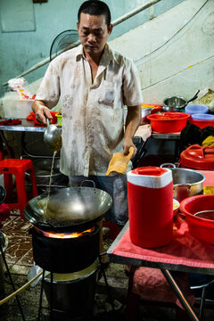 Cook In Saigon's Night Street Food Market Prepares Wok With Hot Oil