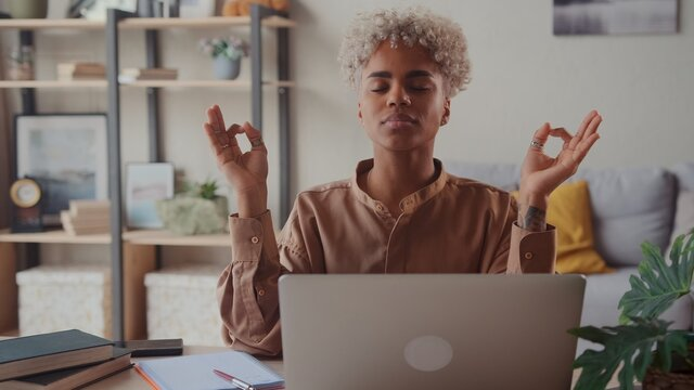 Serene Afro American woman relieving fatigue at workplace make meditation practice closed her eyes makes breathing exercise seated at desk with laptop. No anxiety and stress during workday in office