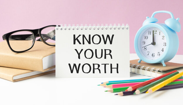 Notepad with text KNOW YOUR WORTH on a white background, near calculator, tablet and pen. Business concept.