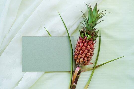 薄緑の布の背景に姫パイナップルでデコレーションした長方形の灰色の厚紙のモックアップ