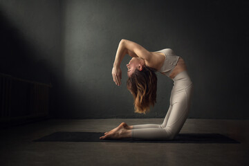 Fototapeta A slim beautifully lighted young  woman is doing Camel yoga pose (Ustrasana) in a dark room. Image with selective focus and toning obraz