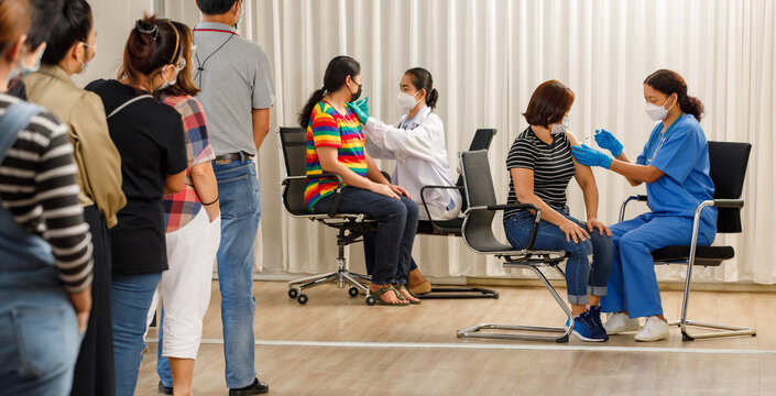 Variety ages citizens standing in a row and waiting for a vaccine injection while medical people injecting to senior women in face mask. Covid-19 or coronavirus  herd immunity concept.