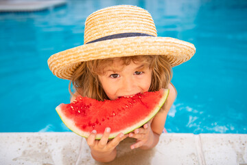 Obraz Portrait of child boy eating a slice of watermelon by a swimming pool having fun playing summer holiday, outdoors. Active kids lifestyle vacation. - fototapety do salonu