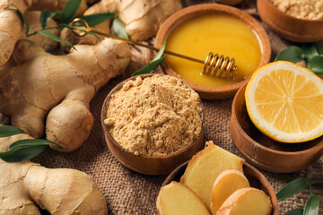 Bowl with ginger powder, honey and lemon on table, closeup