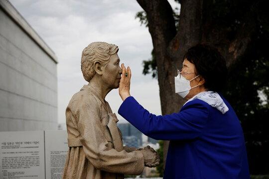 """Former South Korean """"comfort woman"""" Lee Yong-soo looks at a statue symbolising """"comfort women"""" at the Seoul Comfort Women Memorial in Seoul"""