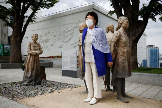 """A former South Korean """"comfort woman"""" poses for photographs at the Seoul Comfort Women Memorial in Seoul"""