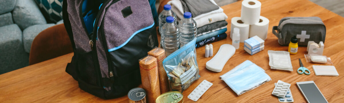 Woman putting cans of food to prepare emergency backpack in living room