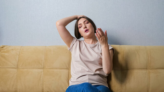 Young woman suffering from heat while sitting on sofa at home.