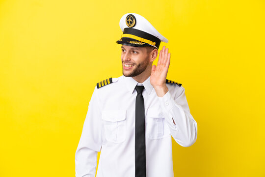 Airplane caucasian pilot isolated on yellow background listening to something by putting hand on the ear