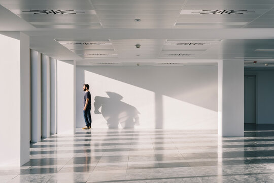 Man standing near window in spacious office hall