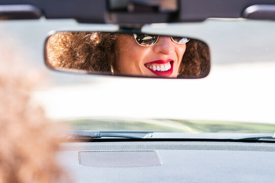 Cheerful woman reflecting in rearview mirror of car