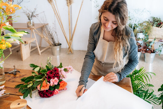 Content young ethnic woman cutting paper while making bouquet of assorted flowers
