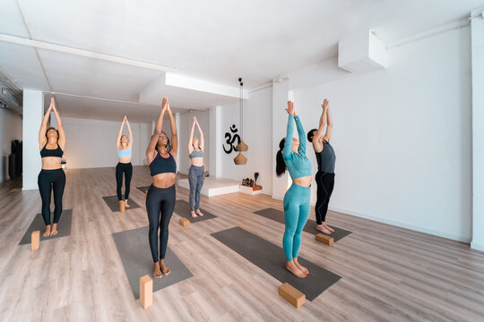 Company of diverse people doing yoga together in studio
