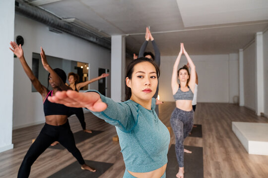 Asian woman doing yoga in Warrior pose during group lesson