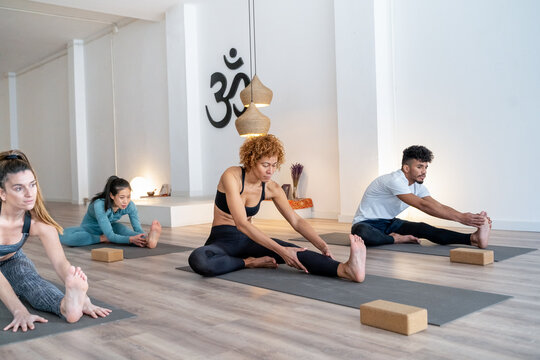 Group of diverse people sitting on mats during yoga class