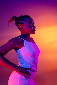 Beautiful African girl in white short summer dress posing isolated over bright colorful neon background.