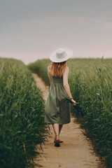Fototapeta Young woman in a hat walking in a wheat field, enjoys life and summer. Wheat field.Healthy lifestyle Concept obraz