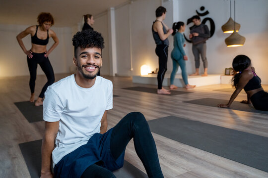 Cheerful black man sitting on mat in yoga studio