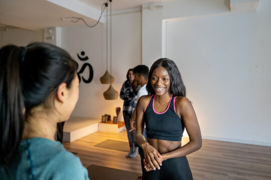 Smiling diverse women talking to each other in yoga studio