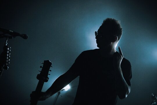 Low Angle View Of Silhouette Man Against Illuminated Light At Night