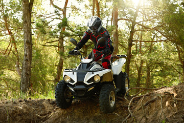 Man driving modern quad bike in forest. Extreme sport