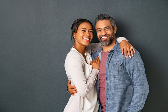 Mature multiethnic couple embracing and smiling together