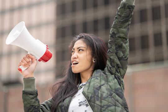 Asian rebel with loudspeaker on street