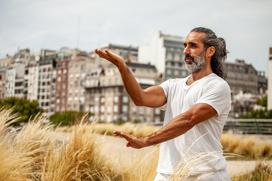 Middle aged Hispanic man practicing yoga in town