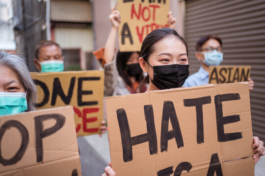 Asian protesters in face masks with placards on city street