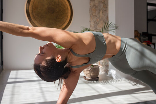 Woman preparing for Wild Thing pose on yoga mat
