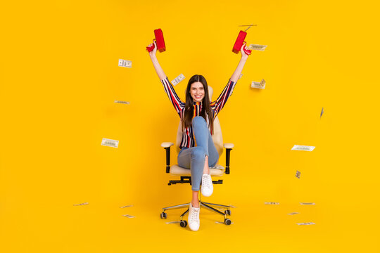 Full body photo of young girl happy smile sit chair shoot movey waste rich dollars air isolated over yellow color background