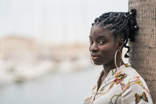 Thoughtful black woman with ethnic braids and earrings looking at camera