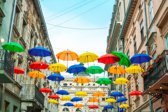 Multicolored open umbrellas hanging on city street by blue sky. Lot of flying parasol and houses in summer Lviv, Ukraine