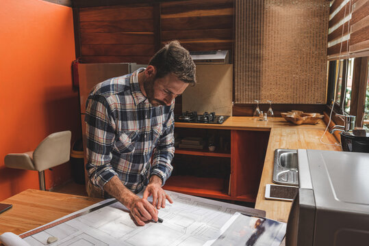 Male architect creating draft of house at table