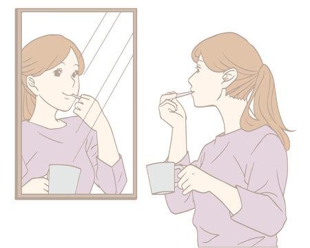 鏡を見て歯みがきをする女性(パステルカラー)