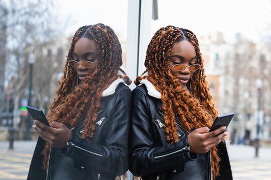 Stylish black woman using smartphone on street