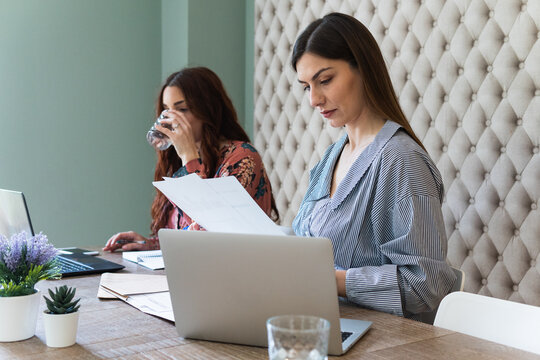 Focused women working on laptops in coworking space